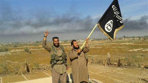 In this photo released on Sunday, June 28, 2015, by a website of Islamic State militants, an Islamic State militant waves his group's flag as he and another celebrate in Fallujah, Iraq, west of Baghdad (Militant website via AP)