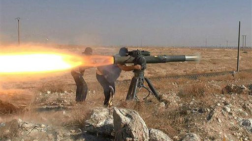 In this picture released on June 26, 2015, by a website of Islamic State militants, Islamic State militants fire an anti-tank missile in Hassakeh, northeast Syria. (Militant website via AP)