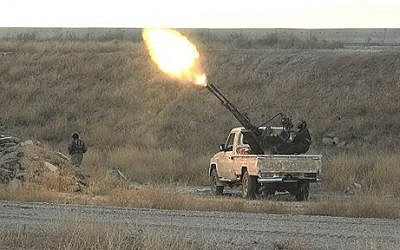 In this photo released on June 26, 2015, by a website of Islamic State militants, an IS fighter fires an anti-aircraft gun from the back of a pickup truck in Hassakeh city, northeast Syria. (IS-affiliated website via AP)