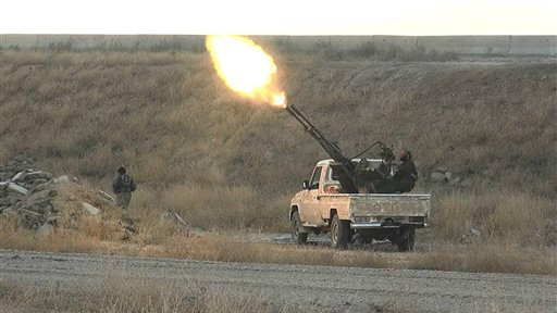 In this photo released on June 26, 2015, by a website of Islamic State militants, an Islamic State militant fires an anti-aircraft gun from the back of a pickup truck in Hassakeh city, northeast Syria (Militant website via AP)