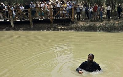 In this Tuesday, April 22, 2008 file photo, a Greek Orthodox Christian priest bathes in the Jordan River after it was blessed during a baptism ceremony at Qasr al-Yahud near Jericho in the West Bank, as people from Jordan's baptismal area, background, also watch the ceremony across the river. (AP Photo/Tara Todras-Whitehill, File)