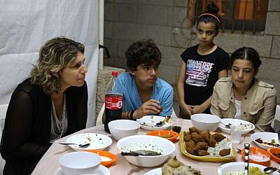 A Jewish mother and three Muslim children sit for an interfaith iftar coordinated by Kids4Peace (Eric Cortellessa/Times of Israel)