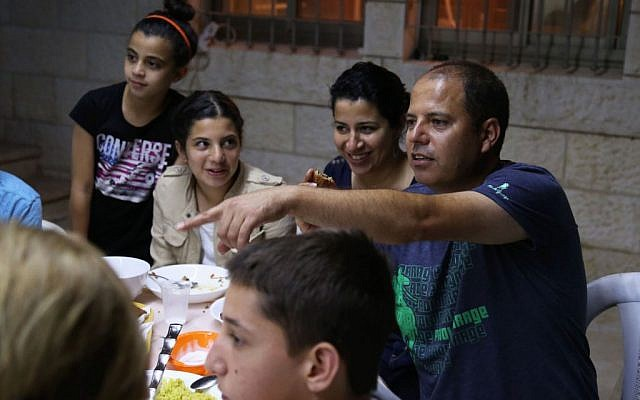 Fayez (right) sits with his wife and daughter, along with three Jewish families for an iftar (Eric Cortellessa/Times of Israel)