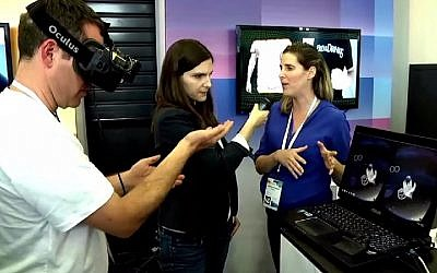 A user (left) demonstrates how the Oculus VR headgear operates with Israel-based start-up Pebbles Interfaces, as Geektime's Laura Rosbrow (center) interviews Pebbles representative Renana Perlovitch. (Geektime)