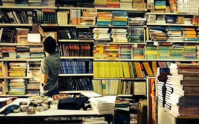 Illustrative image of a boy searching for books in Jerusalem's Intercol school supply store (Jessica Steinberg/Times of Israel)