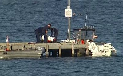 In this image taken from video, police carry a body in a bag and place it in on a stretcher on a jetty in Triabunna, off the Australian island state of Tasmania, on Saturday, July 25, 2015 (AuBC via AP)