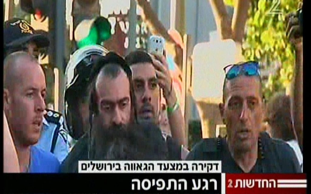 The suspected stabber at a Jerusalem Pride Parade being led away by police on July 30, 2015. (screen capture: Channel 2)