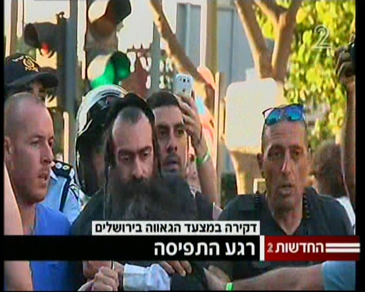 The suspected stabber at a Jerusalem Pride Parade being led away by police on July 30, 2015. (screen capture: Channel 2/Vanesa Kopiler)