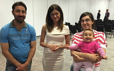 A young Christian Syrian couple with their seven month old daughter flank Miriam Shaded, a Polish church charity worker, who will help the families resettle in Poland, in Warsaw last week. Shaded has a Syrian Christian background and works for the Esther Foundation. (courtesy)