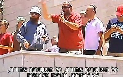 A man whips up the crowd of protesters at Beit El on July 29, 2015 (Channel 2 screenshot)