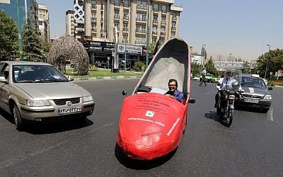 Iranian shoeshine man, Mohammad Ali Hassan Khani, whose nickname is Aliwaxima, drives his racy-red motorized stiletto on a street on August 19, 2015 in the capital Tehran. (AFP PHOTO / ATTA KENARE)