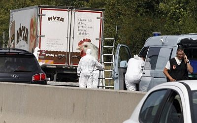 Forensic officers stand in front of a truck inside which were found a large number of dead migrants on a motorway near Neusiedl am See, Austria, on August 27, 2015 (AFP/DIETER NAGL)