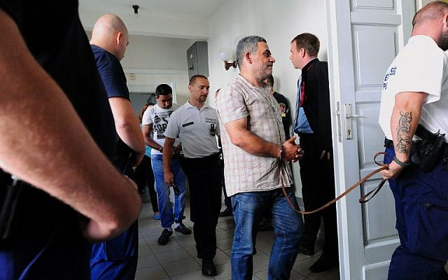 One (C) of four suspects is led by a Hungarian police official into the Kecskemet courtroom on August 29, 2015.  (AFP PHOTO / ATTILA KISBENEDEK)
