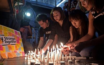 Thai office workers light candles for victims killed in a bomb blast outside a religious shrine in Bangkok on August 18, 2015. (AFP / PORNCHAI KITTIWONGSAKUL)