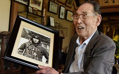 In this photo taken on June 25, 2015, former Japanese fighter pilot Kaname Harada, 98, holds his portrait as a young man as he tells his experience during World War II at his home in Nagano, Japan. (AFP Photo/Toru Yamanaka)