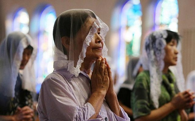 People attend a morning mass for victims of the World War II atomic bombing of Nagasaki at the city's Urakami Cathedral on August 9, 2015. (AFP Photo/Jiji Press)