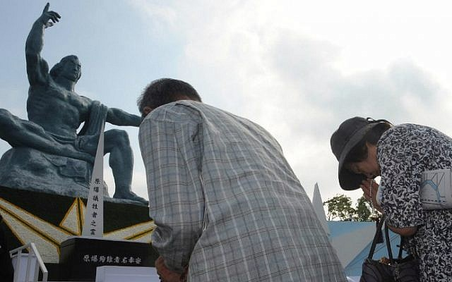 People offer prayers for victims of the World War II atomic bombing of Japan at the Peace Statue in Nagasaki on August 9, 2015. (AFP Photo/Jiji Press)