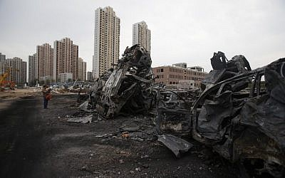 A man takes a photo of damaged cars at the site of the explosions in Tianjin on August 14, 2015.  Enormous explosions in a major Chinese port city killed at least 85 people and injured hundreds more, according to state media (AFP PHOTO)