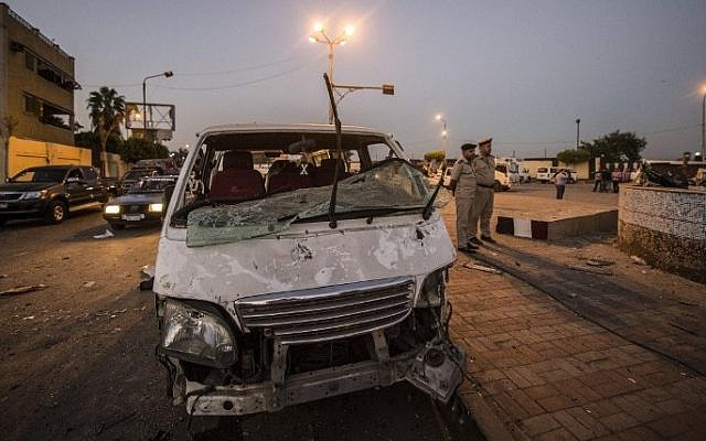 Egyptian policemen (R) stand next to a damaged car in front of a damaged national security building after a bomb blast in northern Cairo's district of Shubra on August 20, 2015.  (AFP  / KHALED DESOUKI)