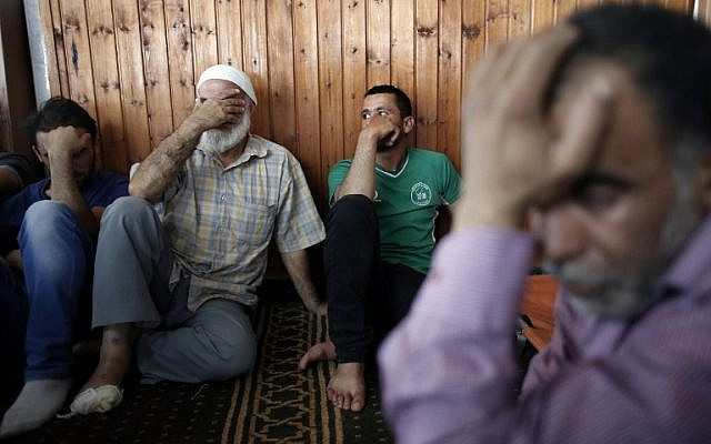 Relatives of 18-month-old Palestinian toddler Ali Saad Dawabsha, who died after his house was set on fire, allegedly by Jewish settlers, mourn next to his body lying at a mosque during his funeral in the West Bank village of Duma on July 31, 2015.  Hussein Dawabsha,  the baby's grandfather is seen on the right. (AFP PHOTO / THOMAS COEX)