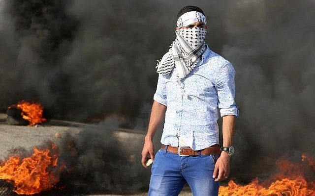 A Palestinian protester stands amid burning tires during clashes with Israeli security forces on a street leading to Duma village, on August 1, 2015 (Jaafar Ashtiyeh/AFP)