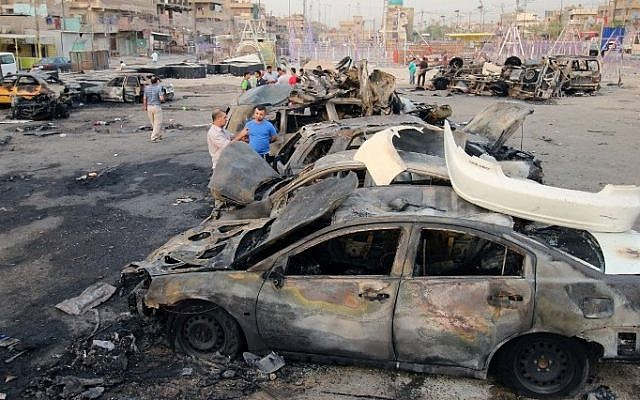 Illustrative: Iraqi men stand next to the wreckage of vehicles in the aftermath of a car bombing at a popular market in Baghdad's northern Shiite district of Sadr City on August 6, 2015.  (AFP/HAIDAR MOHAMMED ALI)