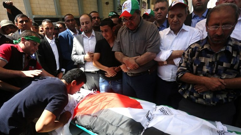 Palestinian men pray over the body of Saad Dawabsha, the father of a Palestinian toddler killed last week when their home was firebombed by Jewish extremists, during his funeral in the West Bank village of Duma on August 8, 2015. (AFP/ JAAFAR ASHTIYEH)