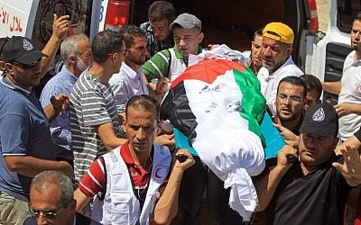 Members of the Palestinian Red Crescent Society carry the body of Saad Dawabsha, the father of a Palestinian toddler killed last week when their home was firebombed by Jewish extremists, during his funeral in the West Bank village of Duma on August 8, 2015. (AFP/ JAAFAR ASHTIYEH)