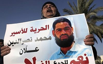 Maazouze, the mother hunger-striking Palestinian prisoner Mohammed Allaan, holds a portrait of her son during a rally calling for his release in the southern Israeli city of Beersheba on August 9, 2015 (Ahmad Gharabli/AFP)