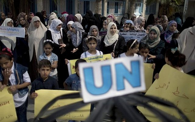 Palestinian children and teachers hold placards during a protest against the reduction of educational programs given by the United Nations Relief and Works Agency at the Rafah refugee camp in the southern Gaza Strip, August 15, 2015. (AFP /SAID KHATIB)