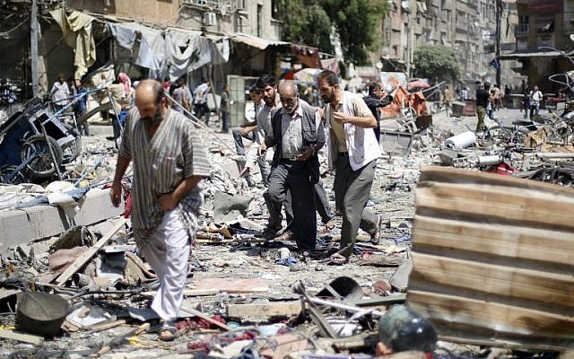 Syrians walk amid the rubble following air strikes by Syrian government forces on a marketplace in the rebel-held area of Douma, east of the capital Damascus, on August 16, 2015. (Sammer al Doumy/AFP)