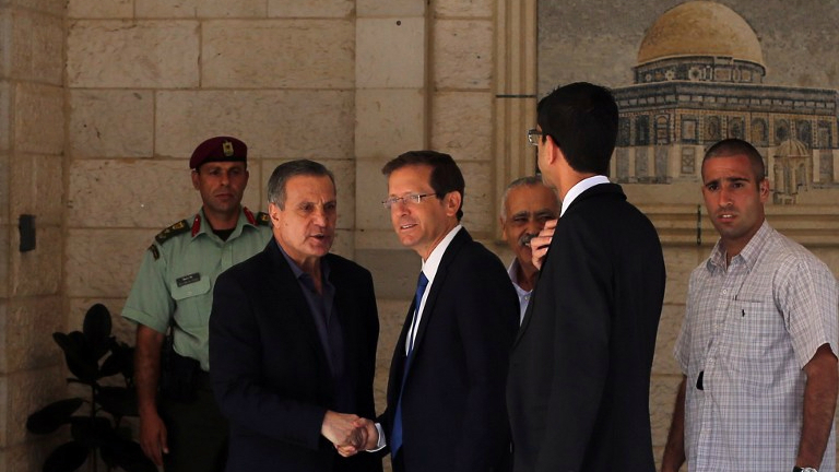 Nabil Abu Rudeineh (L), spokesman of Palestinian Authority president Mahmoud Abbas, welcomes Israeli opposition head Isaac Herzog (C) at the Palestinian Authority headquarters in the West Bank city of Ramallah, August 18, 2015. (AFP Photo/Abbas Momani)