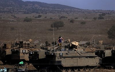 An Israeli soldier stands on top of an armored personnel carrier stationed on the Israeli side of the Golan Heights on August 21, 2015. (AFP Photo/Ahmad Gharabli)