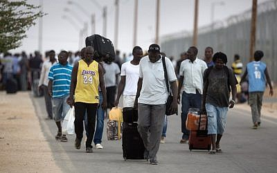 African migrants carry their belongings following their release from the Holot Detention Center in the Negev desert, on August 25, 2015. (AFP PHOTO/MENAHEM KAHANA)