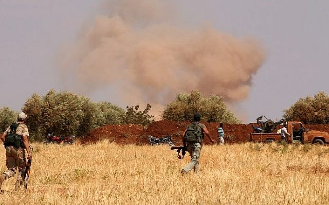 Illustrative photo of Syrian rebel forces from Jaysh al-Islam (Army of Islam) taking position behind a sand barrier, Syria,  August 25, 2015 (AFP/AMC/ZEIN AL-RIFAI)