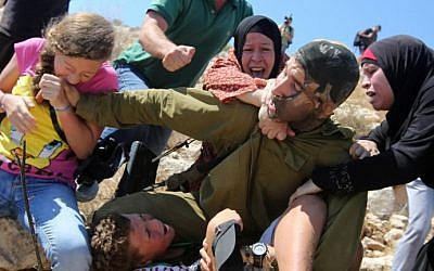 A Palestinian girl (left), bites the hand of an Israeli soldier (center), during clashes between Israeli security forces and Palestinian protesters, in the West Bank village of Nabi Saleh near Ramallah, August 28, 2015. (AFP/Abbas Momani)