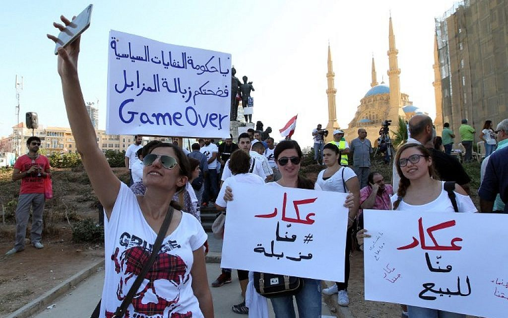 Lebanese young women take pictures as they hold placards before the start of an anti-government protest organised by a civil society frustrated with a political class they see as corrupt and incapable of providing basic services on August 29, 2015 at Beirut's iconic Martyrs Square. (AFP/ ANWAR AMRO)