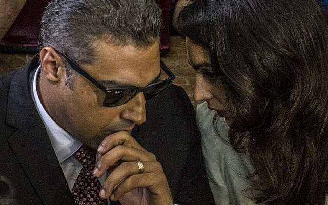 Al-Jazeera journalist, Canadian Mohamed Fahmy (L), accused along with Egyptian Baher Mohamed of supporting the blacklisted Muslim Brotherhood in their coverage for the Qatari-owned broadcaster, talks to human rights lawyer representing him, Amal Clooney (R), during their trial in the capital Cairo on August 29, 2015.(AFP PHOTO / KHALED DESOUKI)