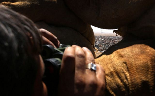 An Iraqi Kurdish Peshmerga fighter monitors the area with binoculars as he holds a position behind sandbags on the front line near the northern Iraqi town of Sinjar, west of Mosul, on August 17, 2015. (AFP Photo/Safin Hamed)