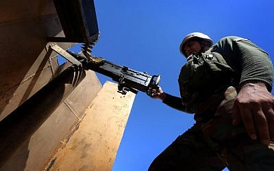 File: An Iraqi Kurdish peshmerga fighter stands behind an armor-plated shield holding a machine gun as he guards a position at the frontline of fighting against Islamic State (IS) militants near the northern Iraqi town of Sinjar, west of the city of Mosul on August 17, 2015. (AFP Photo/Safin Hamed)