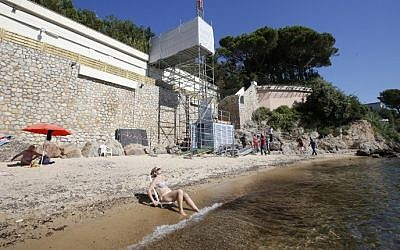 People sit and stand by the water as workers disassemble an elevator on the public beach near the Saudi King's villa in the Golfe-Juan seaside resort in Vallauris, southeastern France, August 3, 2015. (AFP/VALERY HACHE)