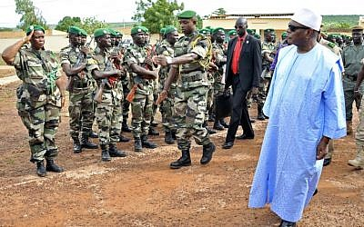 File: Mali's President Ibrahim Boubacar Keita (right) reviews troops in Kati, near Bamako, on August 6, 2015, after visiting soldiers injured in an attack on their camp in northern Mali on August 3, 2015. (AFP/Habibou Kouyate)