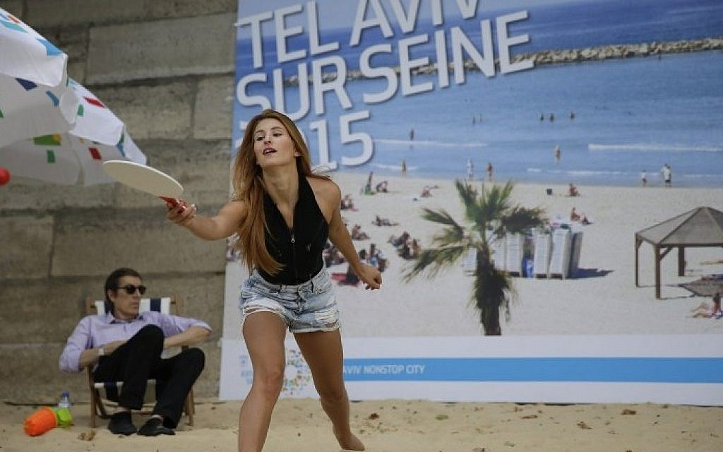 "A woman plays beach tennis at the ""Tel-Aviv sur Seine"" beach attraction as part of the  14th edition of Paris Plages (Paris Beaches) in central Paris, on August 13, 2015. (Kenzo Tribouillard/AFP)"