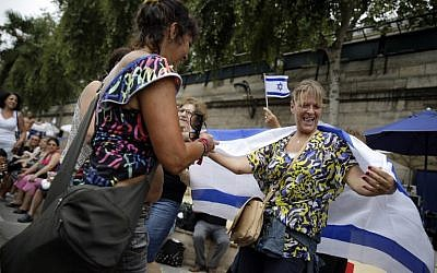 "Women dance with an Israeli flag during ""Tel Aviv Sur Seine"", a beach event celebrating Tel Aviv, in central Paris on August 13, 2015.  (AFP PHOTO / KENZO TRIBOUILLARD)"