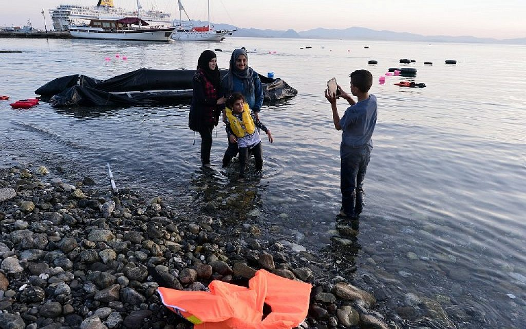 Syrian migrants take a picture after their safe arrival  on an overcrowded dinghy to the coast of the southeastern Greek island of Kos from Turkey, on August 15, 2015. (AFP/LOUISA GOULIAMAKI)