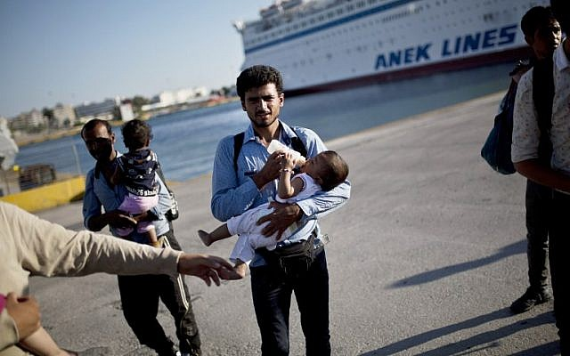 A migrant feeds his child after disembarking from a Greek government-chartered 'Eleftherios Venizelos' ferry at the port of Piraeus in Athens on August 29, 2015. (AFP PHOTO / ANGELOS TZORTZINIS)