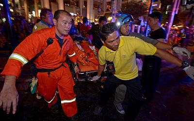 Thai rescue workers carry an injured person after a bomb exploded outside a religious shrine in central Bangkok late on August 17, 2015. (AFP Photo/Pornchai Kittiwongsakul)