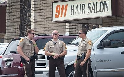 Police stand guard outside the 911 Hair Salon which was looted during a demonstration to mark the first anniversary of the shooting of Michael Brown on August 10, 2015 in Ferguson, Missouri (Scott Olson/Getty Images/AFP)