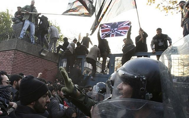 Iranian police officers trying prevent protesters from storming the British Embassy, as others stand on the gates holding a satirized British flag and Islamic flags, in Tehran, Iran, Tuesday, Nov. 29, 2011. (Photo/Vahid Salemi)