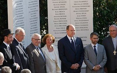 Prince Albert II, 3rd right, stands with French Nazi hunter Serge Klarsfeld, 3rd left, and his wife Beate, center, after unveiling a monument to Jews deported from the Riviera principality during World War II, as part of a larger effort to shed light at last on a troubling chapter in the country's history, in a cemetery in Monaco, Thursday, Aug. 27, 2015. (Claude Paris/AP)